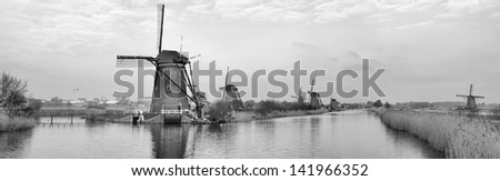 typical dutch windmills at Kinderdijk, Netherlands. The windmills of Kinderdijk are one of the best known Dutch tourist sites. They have been a UNESCO World Heritage Site since 1997. - stock photo