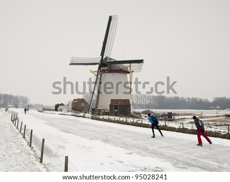 Typical dutch winter: windmill and ice skaters - stock photo