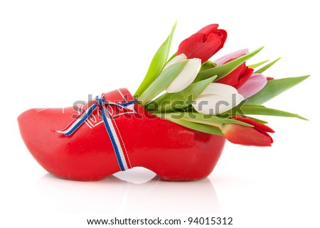 Typical Dutch wooden clog with tulips - stock photo