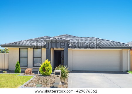 typical  facade of a new  modern suburban  house against blue sky - stock photo