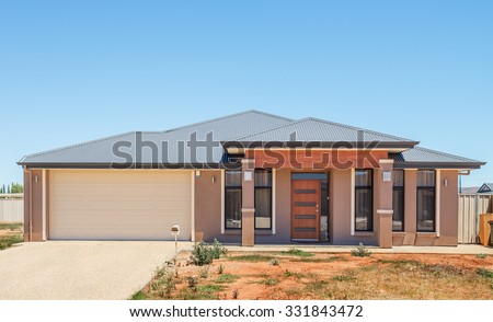 typical  facade of a new suburban  house with not landscaped front yard - stock photo
