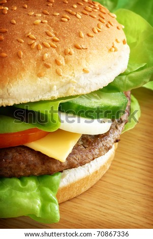 Typical fast food, a burger served with cheese and salad. - stock photo