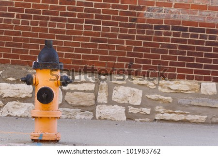 Typical fire hydrant against a brick wall on a city street - stock photo