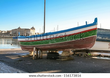 Typical fishing boat in a  port of Siracusa city in Italy - stock photo