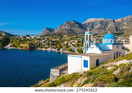Typical for Greece white church with azure-blue dome with peaceful bay in the background on Kalymnos Island, Greece - stock photo