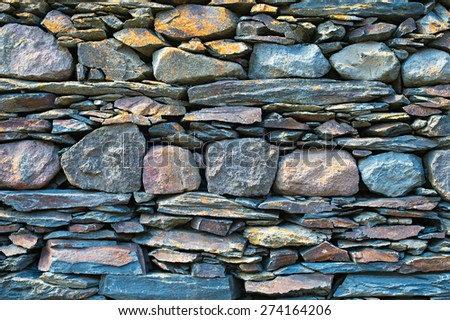 Typical Georgian wall stacked from mountain rocks. Georgia - stock photo