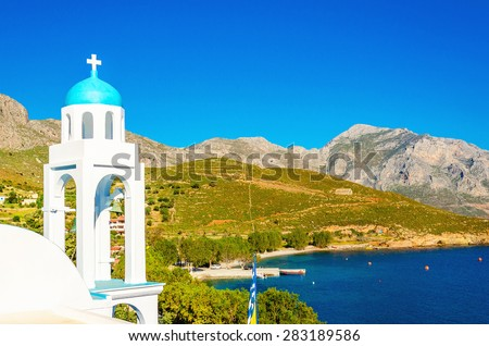 Typical Greek church with blue dome and sea bay in background, southern Greece - stock photo