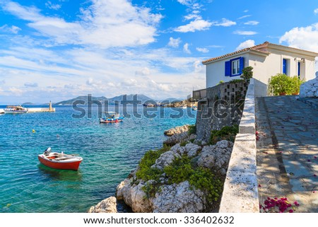 Typical Greek house and fishing boat in Kokkari bay on coast of Samos island, Greece - stock photo