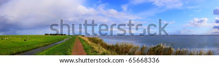 Typical Holland landscape with a small lighthouse on seacoast (Marken. Netherlands) - stock photo
