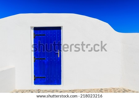Typical house with white walls and blue door in Oia, Santorini Greece - stock photo