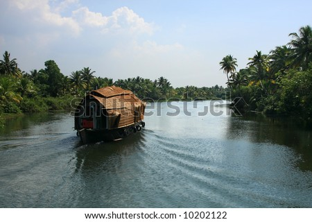 Typical houseboat cruise through the backwaters, Kerala, India. These boats were usually used for goods carrier and was adapted to a luxury boat. - stock photo