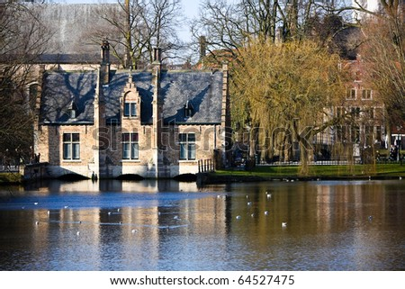 Typical houses in Bruges near Minnewater lake, Belgium - stock photo