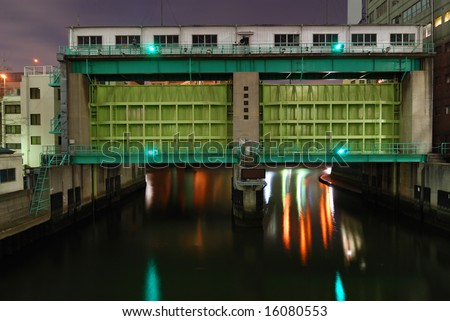 typical huge flood gate in Tokyo metropolis with scenic night illumination - stock photo