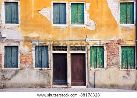 Typical image of exterior of row of houses in Venice, with yellow crumbled stucco on the wall and green wood against the windows