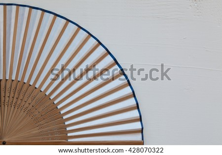 Typical Japanese hand fan made on the wooden white table - stock photo