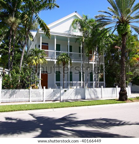 Typical Key-West, Florida house with porches, shutters, and white fence. - stock photo