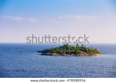 Typical landscape in Karelia - blue sky, clouds, big lake and a lot of distant green islands, trees, stones and rocks