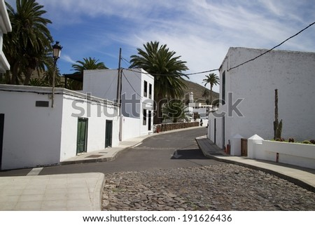 Typical lane between traditional houses in Teguise, Lanzarote island, Spain - stock photo