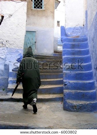 typical man in morocco in a typical street going up stairs
