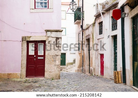 Typical narrow alley in the Alfama district of Lisbon, capital of Portugal, which district is increasingly popular with tourists - stock photo