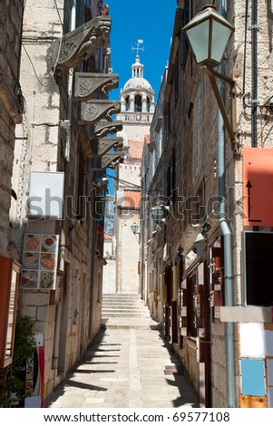 Typical narrow street in old medieval town Korcula by suny day. Croatia, Dalmatia region, Europe. - stock photo