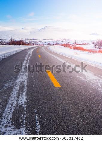 Typical norwegian road in winter - stock photo