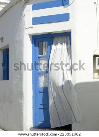 typical old fashioned Greek Island house door with curtain  Chora town Kimilos Greece Cyclades  - stock photo