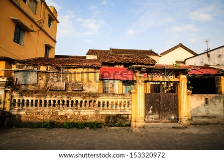Typical old house with yellow wall and roof tiles at Hoi An Ancient Town in early morning sunshine, Quang Nam, Vietnam. Hoi An is recognized as a World Heritage Site by UNESCO. - stock photo