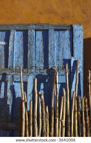 Typical patterns of the american southwest, with adobe clay wall, blue antique door and old wood branch fence.