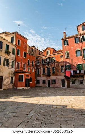 Typical paved campo or urban square in Venice, Italy with colorful historical buildings on a sunny blue sky day - stock photo