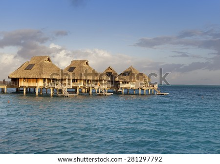 Typical Polynesian landscape -small houses on water. - stock photo