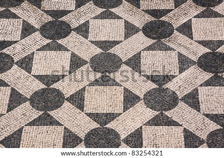 "Typical Portuguese black and white cobble stone mosaic ""calcada""  pavement - Cascais Lisbon Portugal - stock photo"