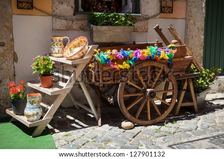 typical portuguese ceramics and small old wooden cart at the doors of a craft shop in Lisbon, Portugal