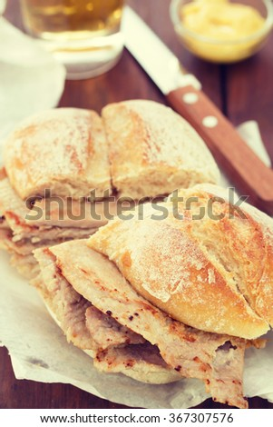 typical portuguese dish bifanas vendas novas with glass of beer on white plate on brown wooden background - stock photo