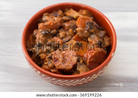 typical portuguese dish feijoada in ceramic bowl on white wooden background
