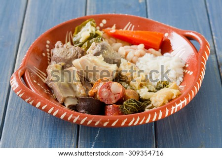 typical portuguese dish on ceramic plate on blue wooden background - stock photo