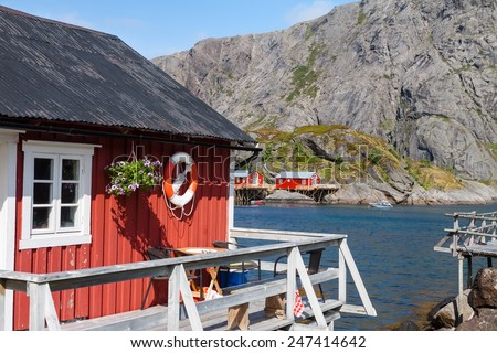 Typical red rorbu, fishing hut invillage Nusfjord on Lofoten islands in Norway lit by midnight sun - stock photo