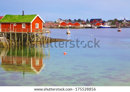 Typical red rorbu hut in fishing harbour in scenic town Reine on Lofoten islands in Norway