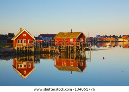 Typical red rorbu huts with sod roof in town of Reine on Lofoten islands in Norway lit by midnight sun - stock photo