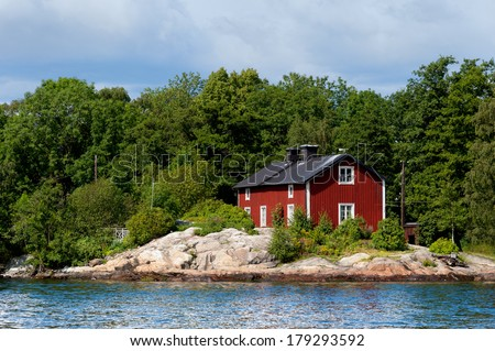 Typical red wooden house in Sweden on a blank polished rock on the shore of the Baltic Sea near the city of Stockholm - stock photo