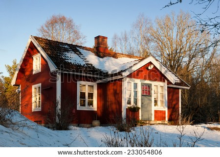 Typical red wooden house in Sweden on a clear and cold winter day - stock photo