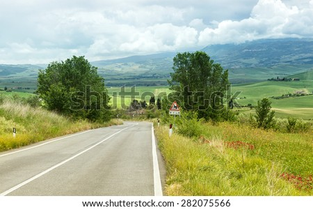 Typical road in the Tuscan hills of the Val d'Orcia. - stock photo