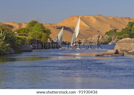 Typical sailing on the Nile. In the background sand hills and blue sky. Near Elephant Island. (Aswan, Egypt).
