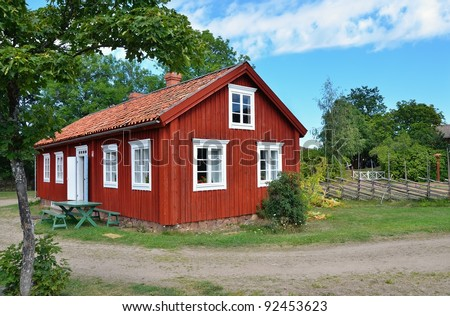 typical scandinavian red wooden  house in village - stock photo