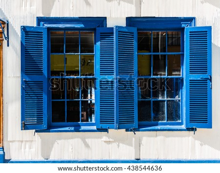 Typical smooth facade covered in zinc and large single-hung sash (guillotine) windows of the houses in Valparaiso, Santa Lucia Hill of historical shell, declared World Heritage by UNESCO. Chile - stock photo