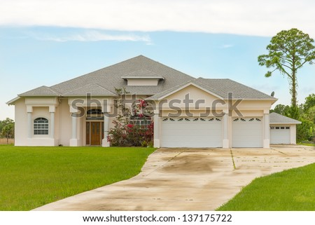 Typical Southwest Florida concrete block and stucco home in the countryside with Bougainvillea flowers, a bahia grass lawn and pine trees. - stock photo