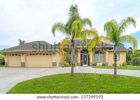 Typical Southwest Florida concrete block and stucco home in the countryside with palm trees, tropical plants and flowers, a bahia grass lawn and pine trees. - stock photo