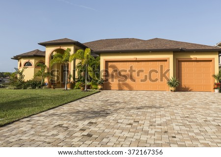 Typical Southwest Florida concrete block and stucco home in the countryside with palm trees, tropical plants and flowers, grass lawn and pine trees. Florida - stock photo