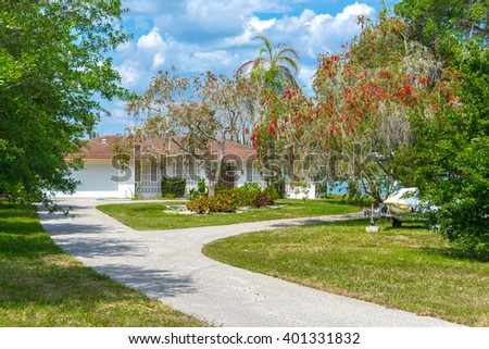 Typical Southwest Florida Concrete Block and Stucco Home on the water with a boat in the yard.  Lovely tropical flowering trees and palms add color to the landscaping.