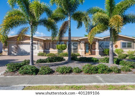 Typical Southwest Florida Concrete Block and Stucco Retirement Home.  Clear hurricane shutters on the windows and palm trees in the landscape.